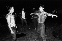 2008.099.011 B & W photo on set of The Outsiders; from left: Emilio Estevez, Rob Lowe (in white t-shirt), Tom Cruise (raised arms) C. Thomas Howell behind Cruise, neck bent over c. 1982. Photo by Dave Kraus/Tulsa Tribune.